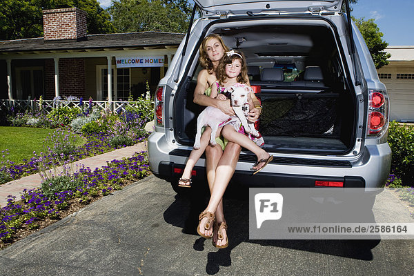 Mother and daughter with puppy sitting in back of Honda Pilot
