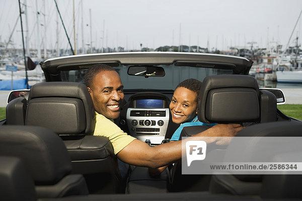 Paar in BMW 650i in marina