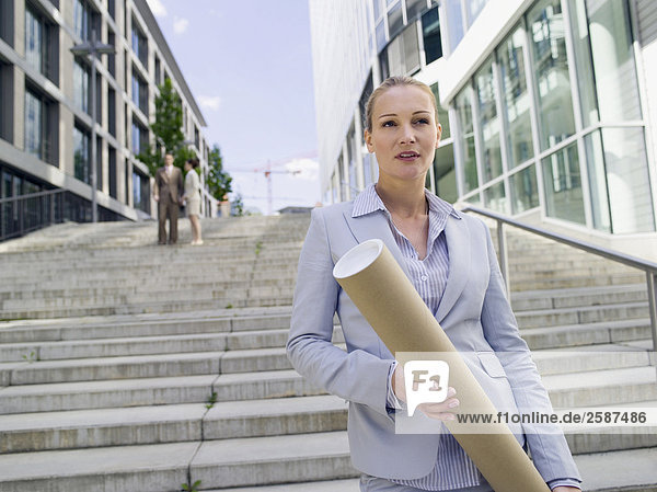 Businesswoman with roll  businesspeople in background