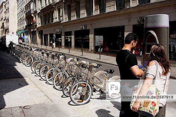 Frankreich. Paris. Ein paar arbeitet an der Muni_meters  ein Fahrrad von einem ´Velib´ Fahrrad entfernt auf der Straße von Paris zu mieten. ´Velib´ ist eine neue Self_service Fahrrad Transit Systemstart  während Mitte Juli 2007 Pariser und Besucher dienen. 2007