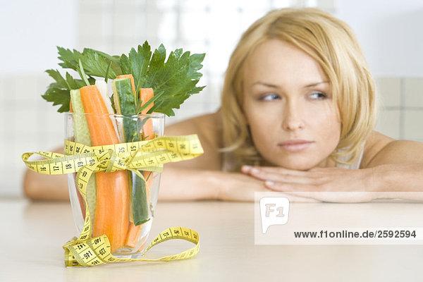 Frau betrachtet Glas gefüllt mit frischem Gemüse  umwickelt mit Maßband in Schleife gebunden Frau betrachtet Glas gefüllt mit frischem Gemüse, umwickelt mit Maßband in Schleife gebunden