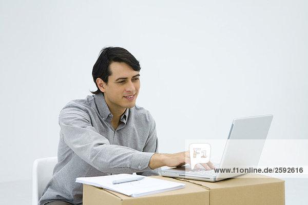 Mann  der am Schreibtisch sitzt und einen Laptop benutzt.