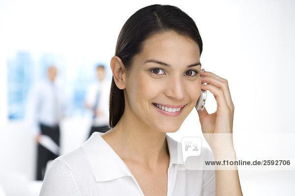 Professionelle Frau mit Handy  lächelnd vor der Kamera