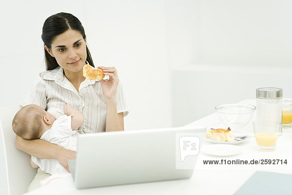 Mutter Stillen Baby am Frühstückstisch  Blick auf Laptop-Computer