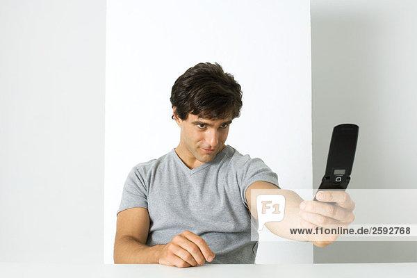 Mann fotografiert sich selbst mit dem Handy