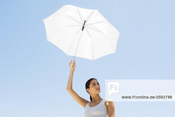Frau hält Sonnenschirm hoch  schaut weg