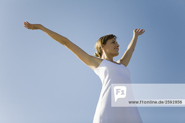 Woman standing outdoors with arms raised  smiling  low angle view
