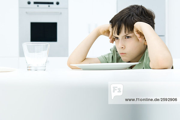 Boy sitting at dinner table  holding head  sulking