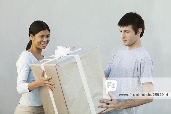 Paar hält großes Geschenk zusammen  lächelnd