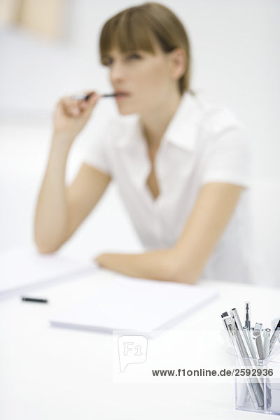 Woman seated at desk  pen in mouth  focus on container full of pens in foreground