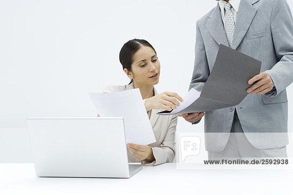 Geschäftsfrau sitzt am Schreibtisch und bespricht das Dokument mit einem männlichen Kollegen.