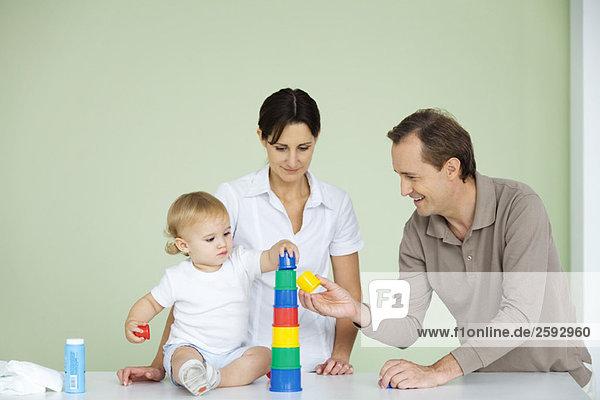 Kleinkind stapelt Plastikspielzeug  Eltern schauen zu
