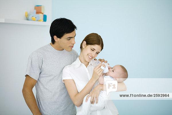 Mutter füttert Baby mit einer Flasche  Ehemann wacht über ihre Schulter
