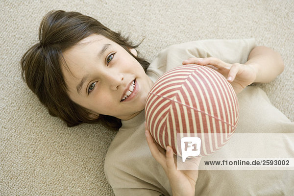 Boy lying on the ground  holding ball  smiling at camera