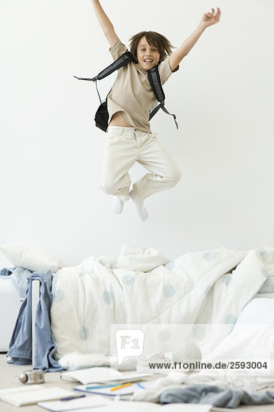 Boy jumping on bed in messy room  arms raised