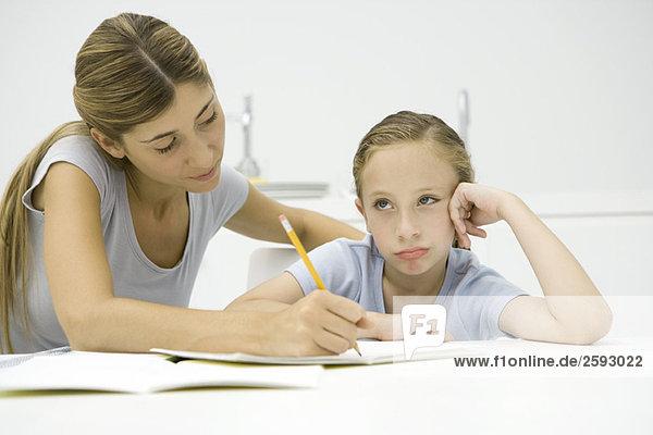 Mutter hilft Tochter bei den Hausaufgaben  Mädchen schaut weg und schmollt.