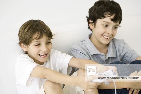 Two boys playing video game together  one holding controller  both smiling