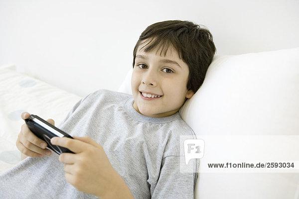 Boy reclining  playing handheld video game  smiling at camera