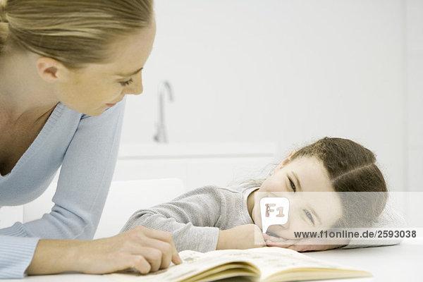 Mutter und Tochter schauen gemeinsam auf das Buch  Mädchen ruht mit dem Kopf auf den Armen