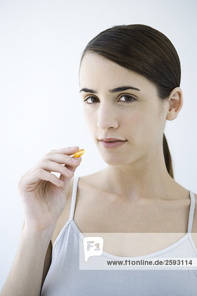 Frau hält Medikamentenkapsel hoch  schaut in die Kamera