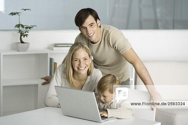 Familie versammelt um Laptop-Computer  kleiner Junge beim Tippen  Eltern lächeln vor der Kamera