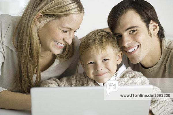 Familie versammelt um Laptop-Computer  Vater und Sohn lächelnd vor der Kamera