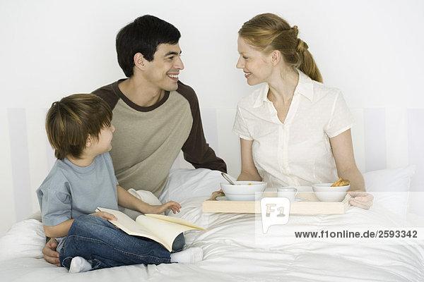 Vater und Sohn geben Mutter Frühstück im Bett