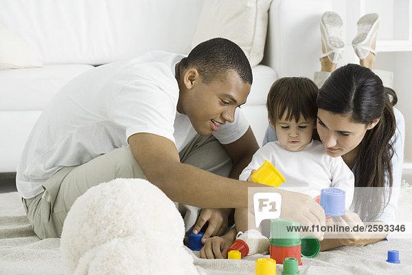 Eltern und Kleinkind spielen mit Bausteinen auf dem Boden