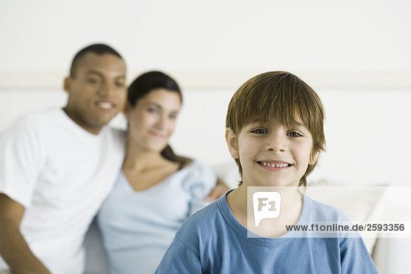 Junge lächelt in die Kamera  Eltern sitzen im Hintergrund