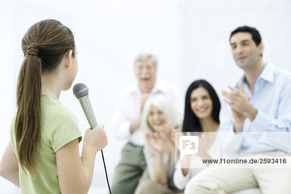 Mädchen-Haltemikrofon  Familienklatschen im Hintergrund