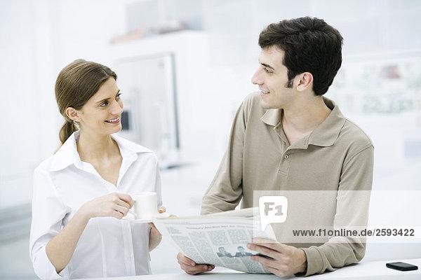 Paar lächelt sich an  Mann hält Zeitung  Frau hält Kaffeetasse