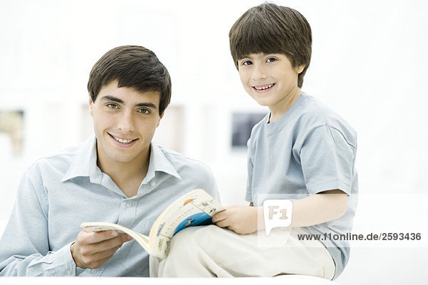 Father and son reading book together  smiling at camera