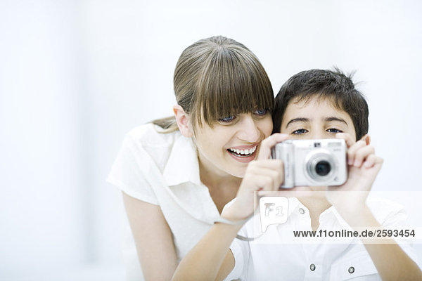 Boy taking picture with camera  mother leaning over his shoulder  smiling