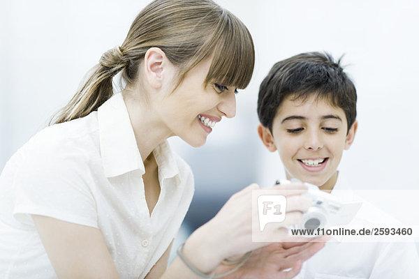 Mutter und Sohn schauen gemeinsam auf die Digitalkamera  lächelnd