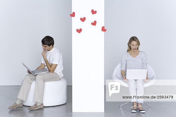 Mann und Frau benutzen Laptops  Herzen schweben in der Luft zwischen ihnen.