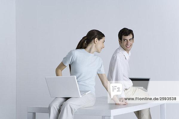 Ein Paar sitzt Rücken an Rücken mit Laptops auf dem Schoß  hält sich an den Händen und lächelt sich an.
