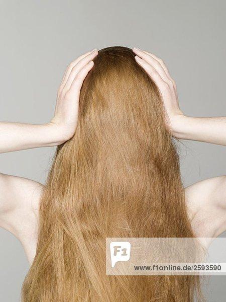 Eine junge nackte Frau mit ihren Haaren  die ihr Gesicht und ihre Hände auf dem Kopf bedecken.