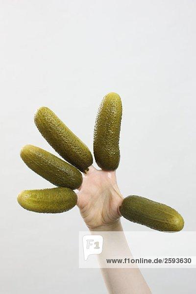 Eine Hand mit Gurken an den Fingern