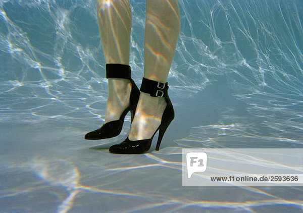 Die Beine einer Frau mit hohen Absätzen unter Wasser