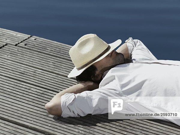 Ein junger Mann  der auf einem Steg liegt.