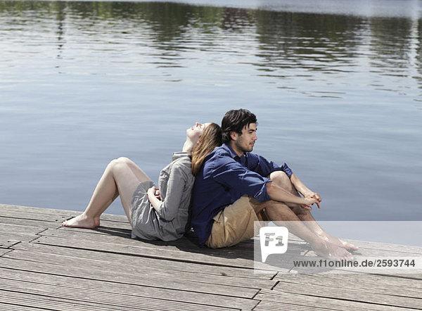 Ein junges Paar  das Rücken an Rücken auf einem Steg sitzt.