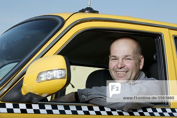 A taxi driver sitting in his car and smiling