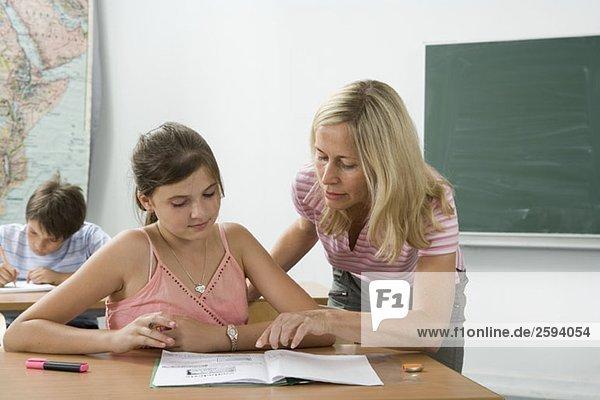 Ein Lehrer hilft einem Schüler im Klassenzimmer.