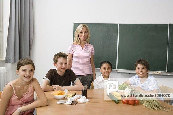 Ein Lehrer und vier Schüler  die etwas über Ernährung lernen.