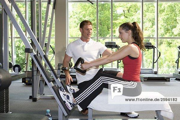 Eine Frau  die eine Gewichtsmaschine mit einem Personal Trainer benutzt.