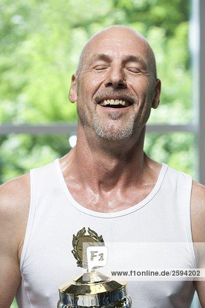 Ein Mann mit einer Trophäe für Gymnastik