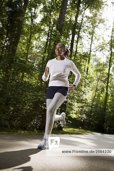 A woman jogging through wooded park