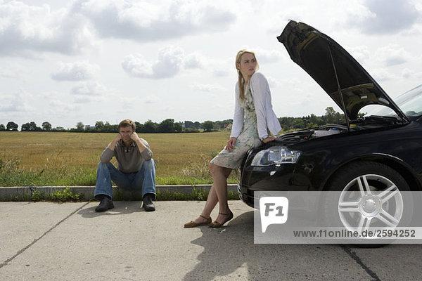 Ein Ehepaar wartet am Straßenrand auf Hilfe mit dem Auto
