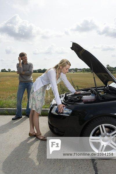 Ein Paar steht am Straßenrand neben ihrem kaputten Auto.