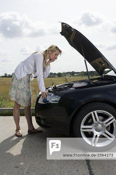 Eine Frau  die sich über eine offene Motorhaube am Straßenrand lehnt.